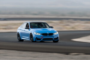 Yas Marina Blue BMW M3 cornering hard at Club Racer Events' debut at Chuckwalla Valley Raceway in California, motorsports photography by Luke Munnell