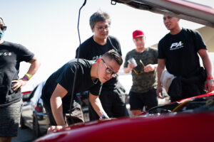 The crew inspects an engine at Club Racer Events' debut at Chuckwalla Valley Raceway in California, motorsports photography by Luke Munnell