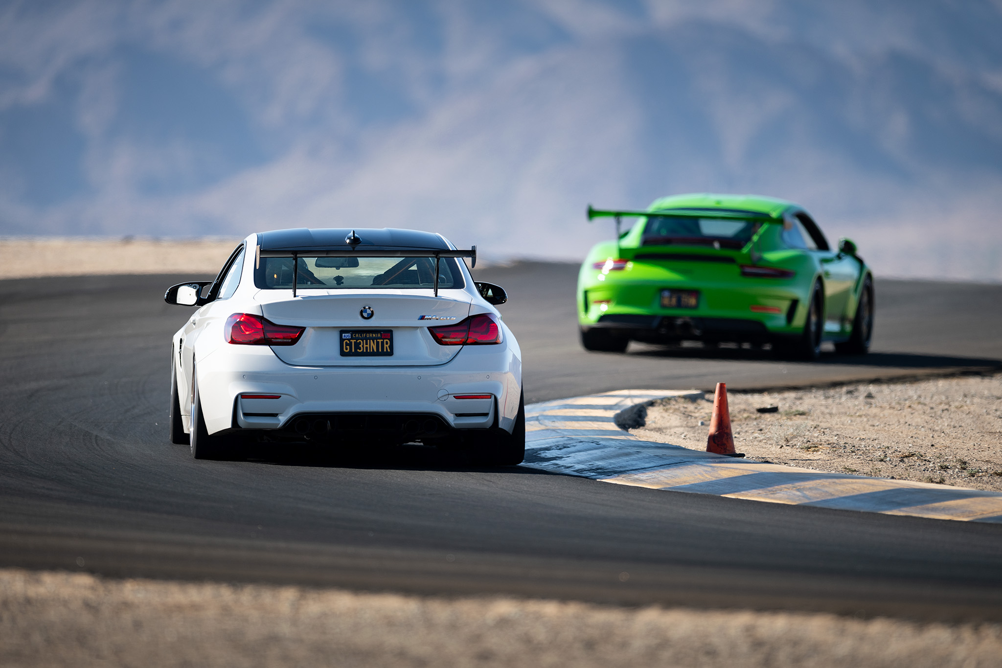 A BMW M4 GTS chases down a Porsche GT3 RS at Club Racer Events' debut at Chuckwalla Valley Raceway in California, motorsports photography by Luke Munnell
