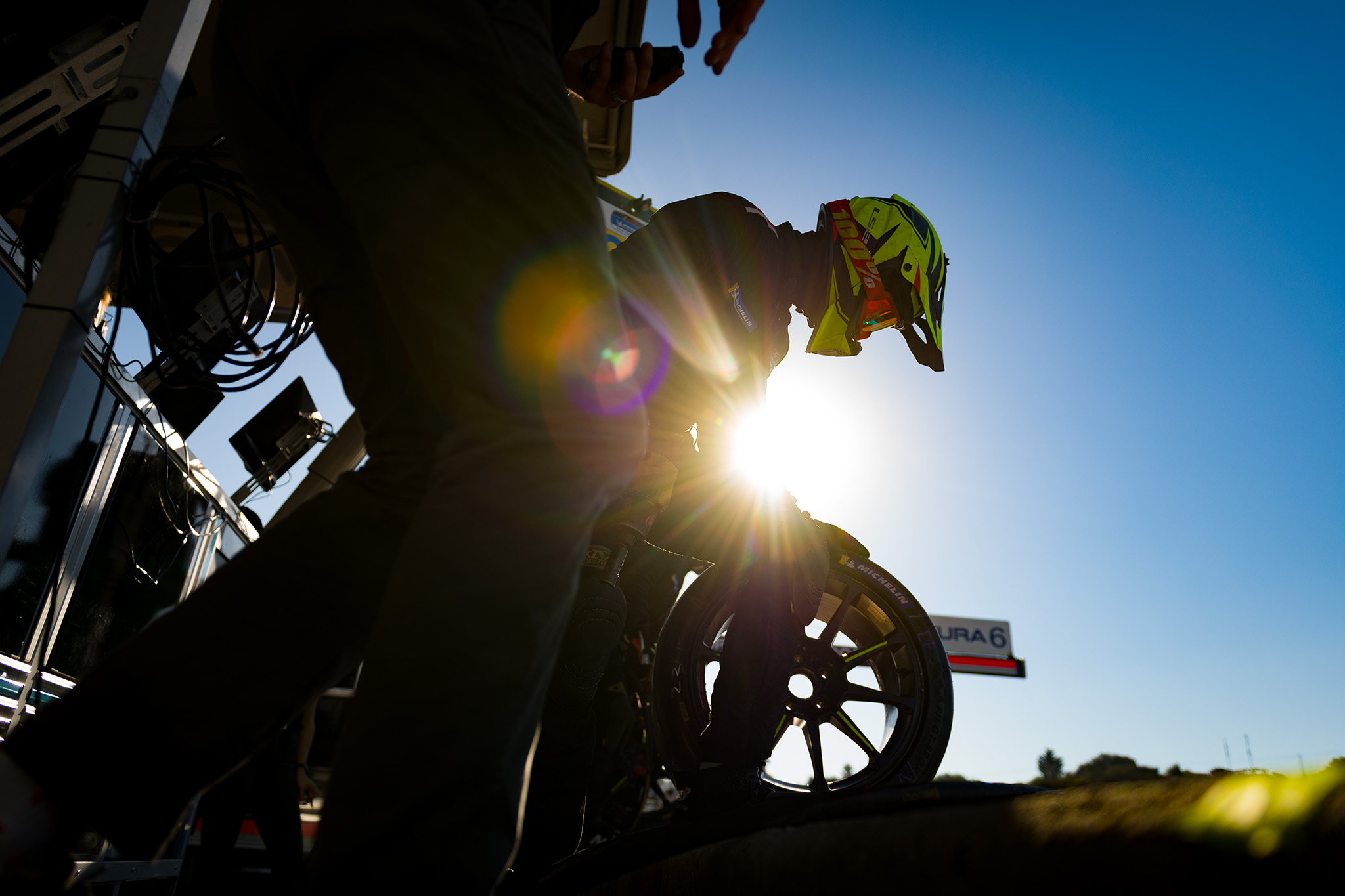 Silhouette of FastMD pit crew ahead of a tire change at IMSA Laguna Seca, motorsports photography by Luke Munnell