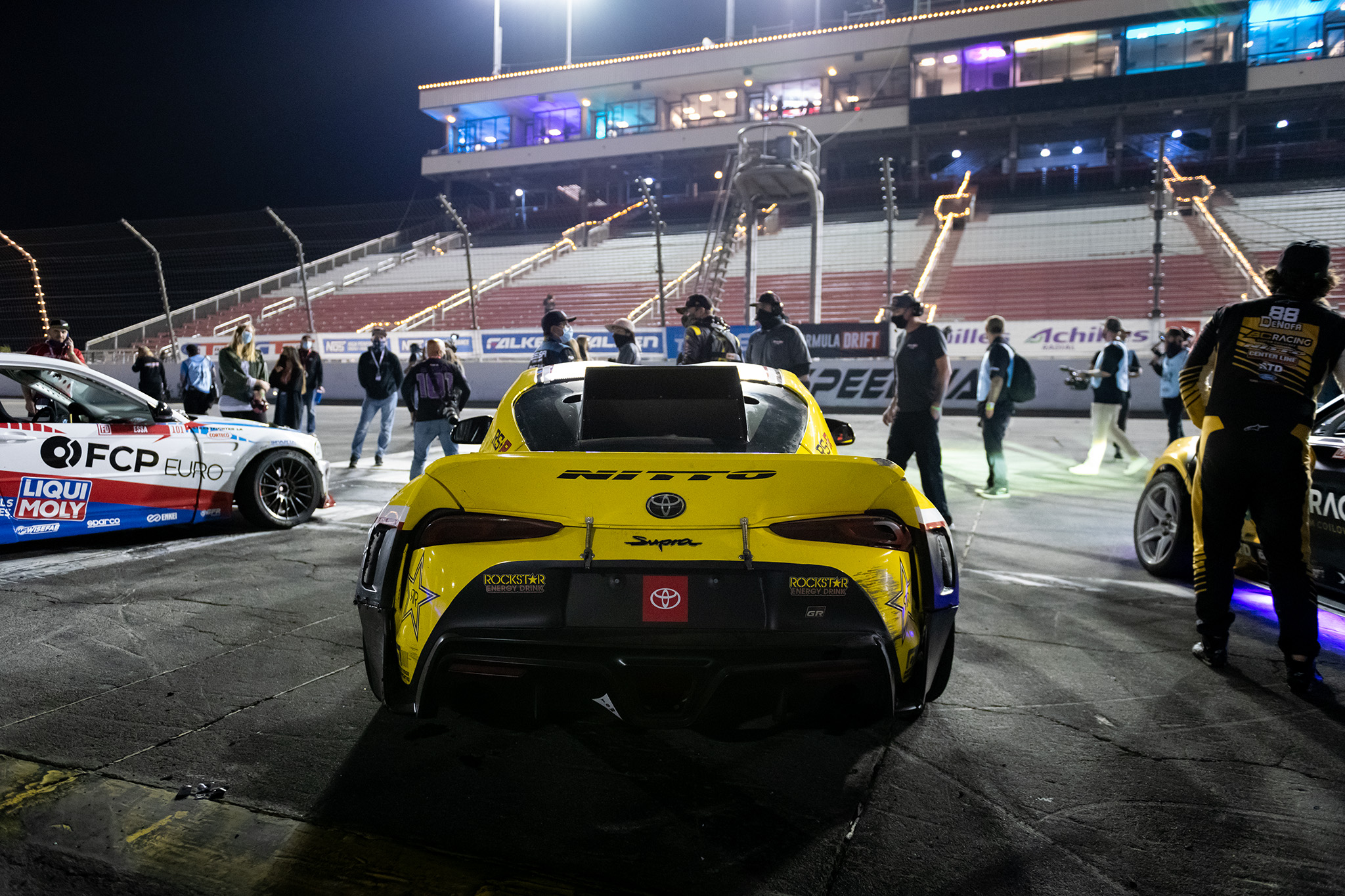 Fredric Aasbo's Papadakis Racing Toyota GR Supra, flanked by Michael Essa's EA BMW E40 M3 and Chelsea DeNofa's BC Racing Nitto Tire Ford Mustang RTR in front of empty Irwindale stands, motorsports photography by Luke Munnell